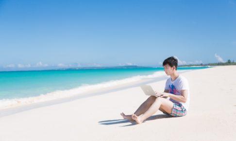 海で楽しそうに泳ぐ同僚を見ながら、ひざの上にMacBook Airを乗せて改修案件をするエンジニア