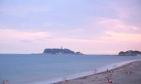 夕焼けの江ノ島と砂浜で楽しむ人々