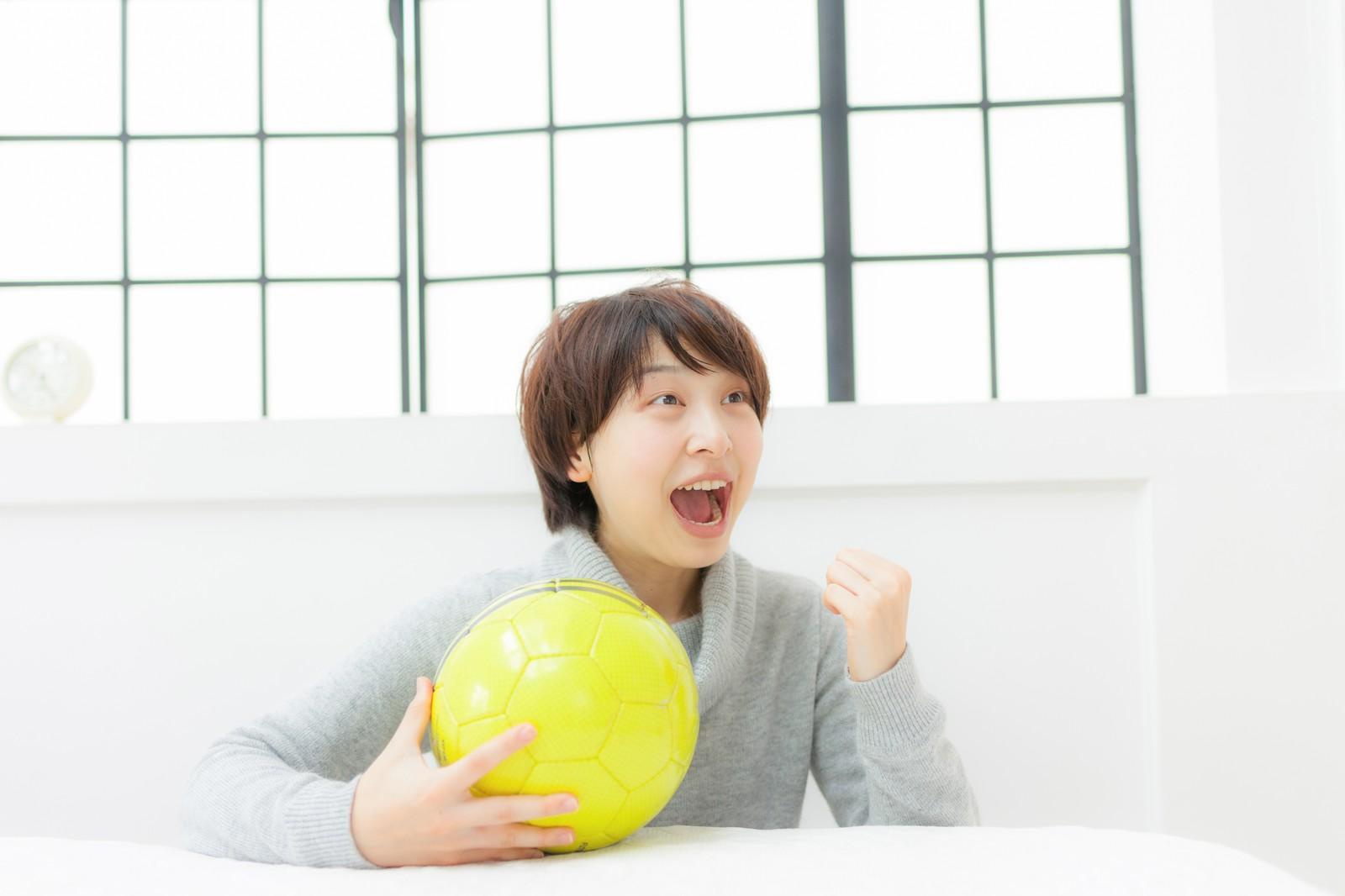 サッカー日本代表の試合をテレビ観戦する女性
